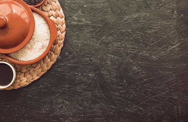 Tigela de grãos de arroz cru no placemat sobre o plano de fundo texturizado áspero