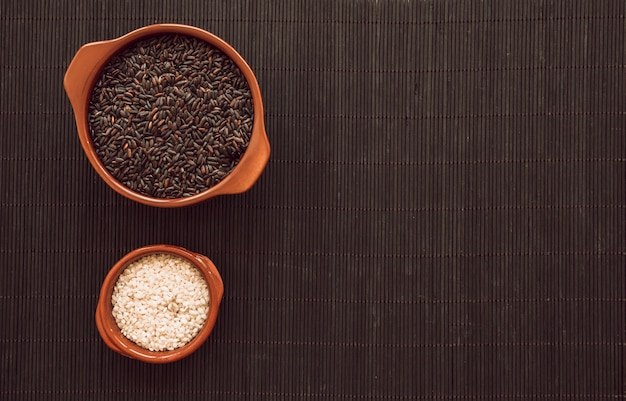 Tigela de grãos de arroz preto e branco na placemat de madeira
