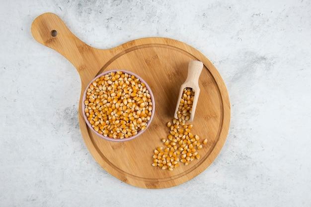 Tigela de grãos de milho cru com colher na placa de madeira.