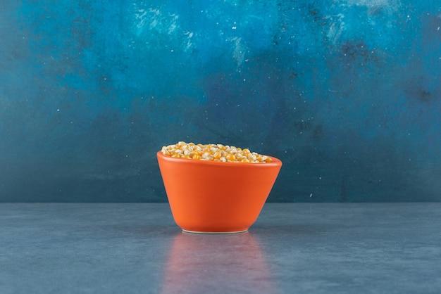Tigela de grãos de milho palced como a peça central em fundo azul. foto de alta qualidade