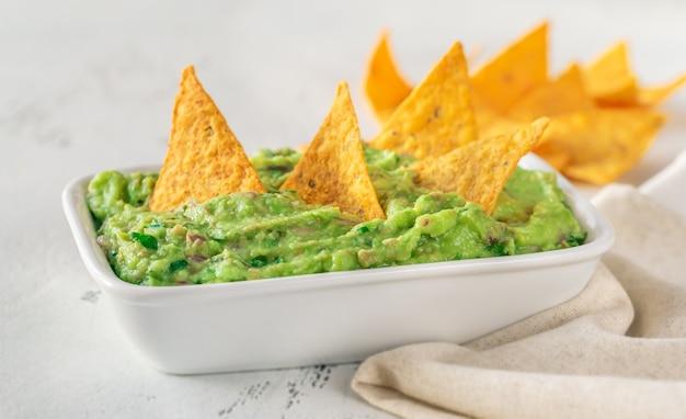 Tigela de guacamole com chips de tortilha na mesa