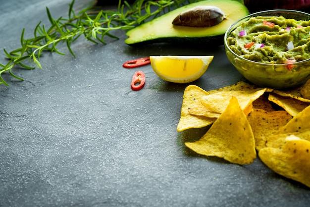 Tigela de guacamole com ingredientes e chips de tortilha em uma mesa de pedra. foco seletivo. copyspace