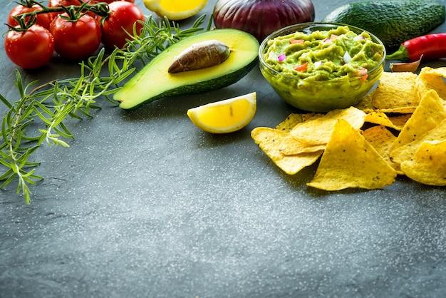 Tigela de guacamole com ingredientes e chips de tortilha em uma mesa de pedra.