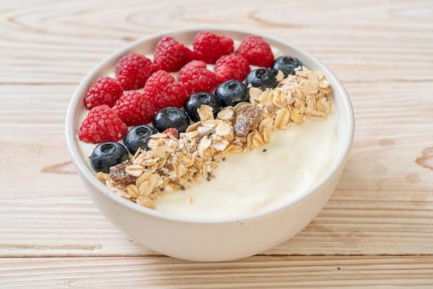 Tigela de iogurte caseiro com framboesa, mirtilo e granola - estilo de comida saudável