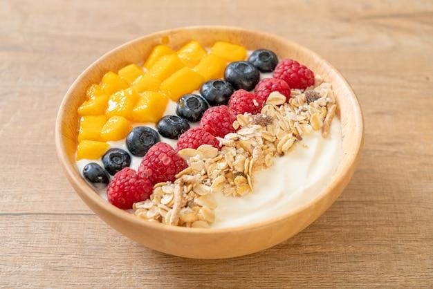 Tigela de iogurte caseiro com framboesa, mirtilo, manga e granola - estilo de comida saudável