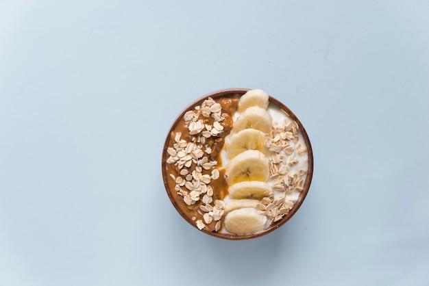 Tigela de iogurte com manteiga de amendoim, banana e aveia