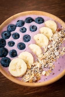 Tigela de iogurte ou vitamina de iogurte com baga azul, banana e granola - estilo de comida saudável