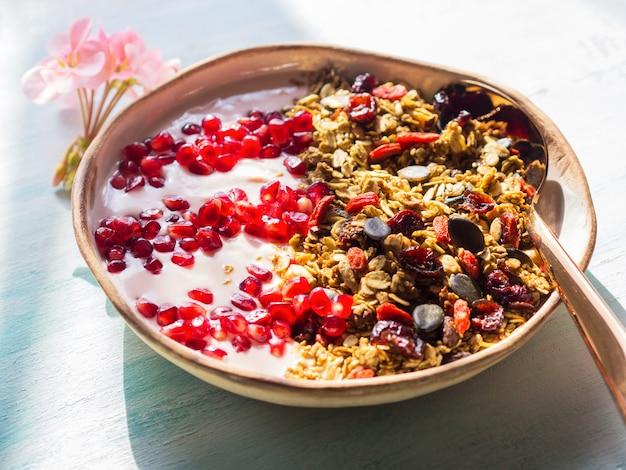 Tigela de iogurte saudável com granola e romã