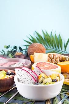 Tigela de iogurte verde pequeno-almoço coberto com pitaya, abacaxi, sementes de chia e bagas com folha de palmeira sobre fundo de pedra, vista superior