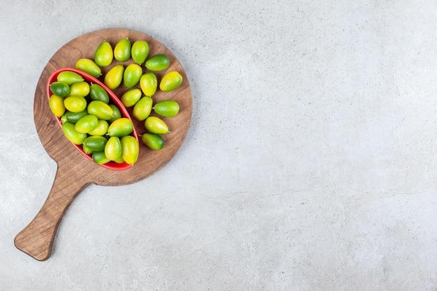 Tigela de kumquats ao lado de uma pilha em uma placa de madeira com fundo de mármore. foto de alta qualidade