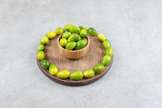 Tigela de kumquats rodeada por um anel de kumquat em uma placa de madeira com fundo de mármore. foto de alta qualidade