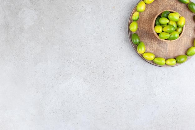 Tigela de kumquats rodeada por um círculo de kumquats em uma placa de madeira com fundo de mármore. foto de alta qualidade
