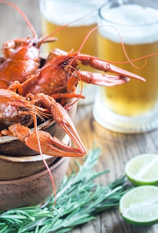Tigela de lagostim cozido com duas canecas de cerveja