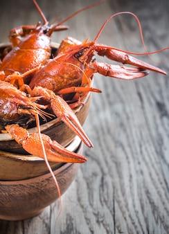Tigela de lagostins cozidos na mesa de madeira