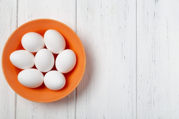 Tigela de laranja com ovos brancos na mesa de madeira com espaço de cópia
