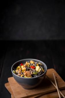 Tigela de macarrão com legumes e pauzinhos