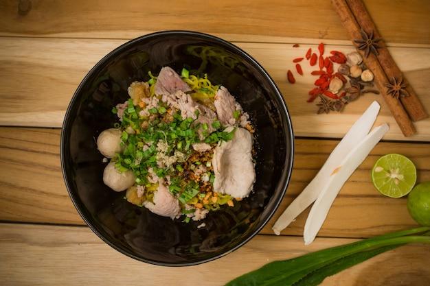 Tigela de macarrão com legumes na mesa de madeira. macarrão delicioso. macarrão instantâneo.
