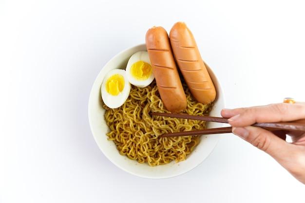 Tigela de macarrão com ovo e salsicha isolada no fundo branco