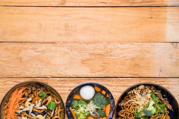 Tigela de macarrão com sopa de bola de peixe na mesa de madeira com espaço de cópia