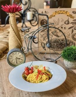 Tigela de macarrão em uma mesa de madeira com uma bicicleta decorativa e uma caixa de pizza