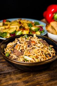 Tigela de macarrão frito mexa com bifes na mesa de madeira