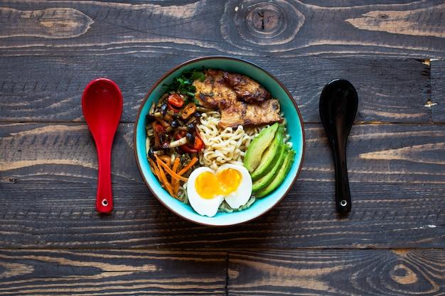 Tigela de macarrão japonês com frango, cenoura, abacate