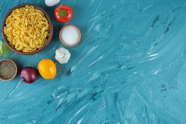 Tigela de macarrão seco cru e legumes frescos sobre fundo azul.