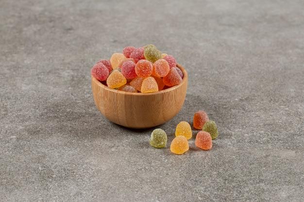 Tigela de madeira cheia com deliciosas marmeladas coloridas.