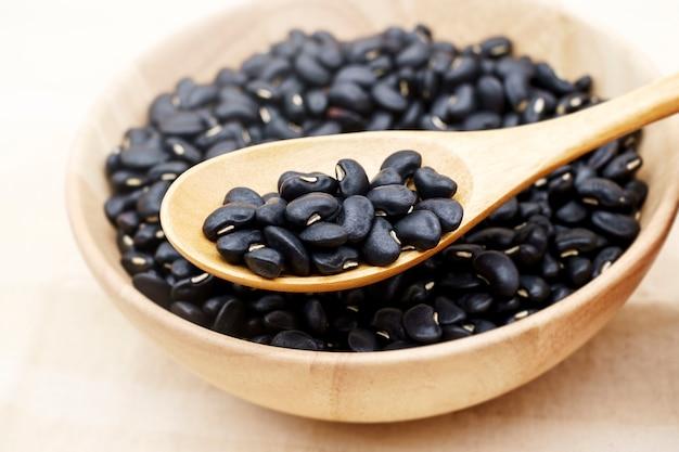 Tigela de madeira cheia de feijão preto seco