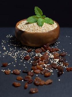 Tigela de madeira cheia de quinoa em preto