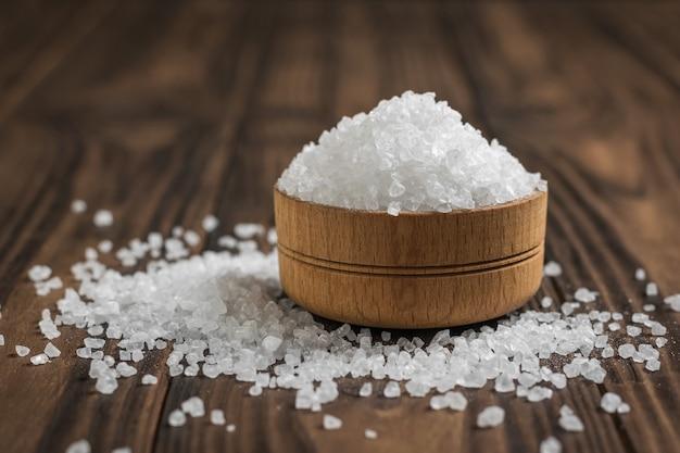 Tigela de madeira cheia de sal grosso em uma mesa de madeira. sal marinho em pedra.