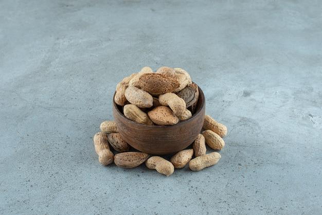 Tigela de madeira com amendoim crocante colocada sobre fundo de pedra