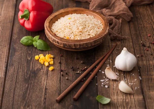 Tigela de madeira com arroz basmati de grão longo cozido com legumes no fundo da mesa de madeira com palitos e páprica vermelha com milho, alho e manjericão.