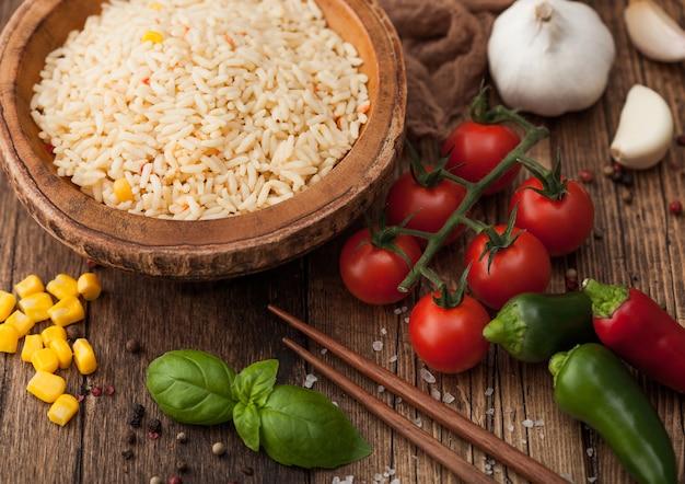 Tigela de madeira com arroz basmati de grão longo cozido com legumes no fundo da mesa de madeira com palitos e tomates com milho, alho e manjericão.