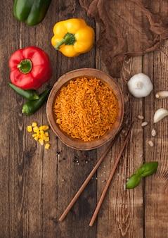 Tigela de madeira com arroz basmati de grão longo vermelho cozido com legumes em fundo de madeira com palitos e pimenta páprica com milho, alho e manjericão.