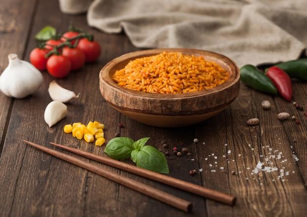 Tigela de madeira com arroz basmati de grão longo vermelho cozido com legumes no fundo da mesa de madeira com palitos e tomates com milho, alho e manjericão com pimenta.