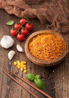 Tigela de madeira com arroz basmati de grão longo vermelho cozido com legumes no fundo da mesa de madeira com palitos e tomates com milho, alho e manjericão.