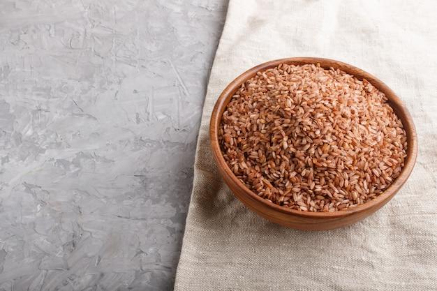 Tigela de madeira com arroz integral não polido. vista lateral, copyspace.