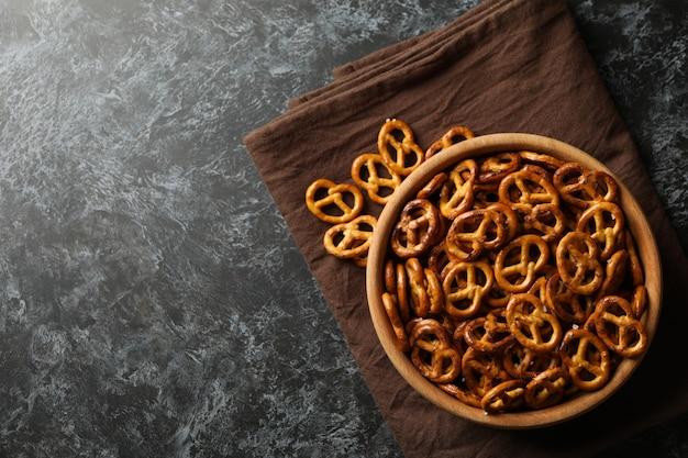 Tigela de madeira com bolachas saborosas pretzels no guardanapo