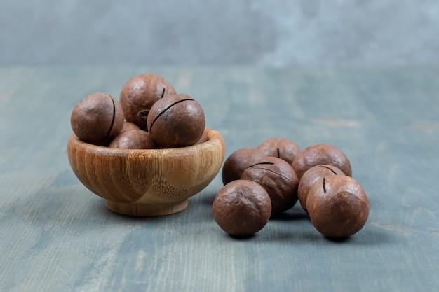 Tigela de madeira com bolas de chocolate colocadas numa superfície de madeira.