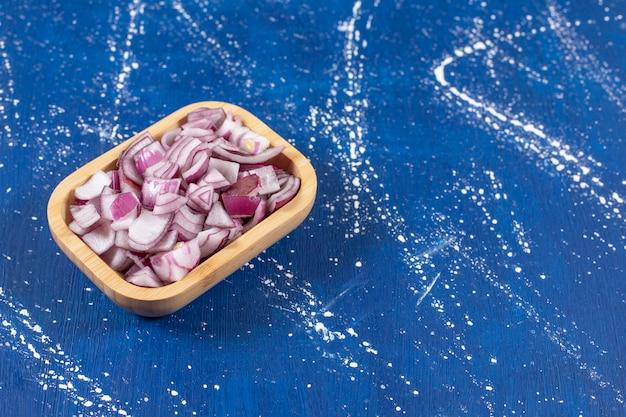 Tigela de madeira com cebolas roxas fatiadas na superfície de mármore.