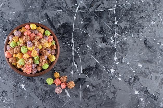 Tigela de madeira com deliciosas pipocas coloridas na mesa de mármore.