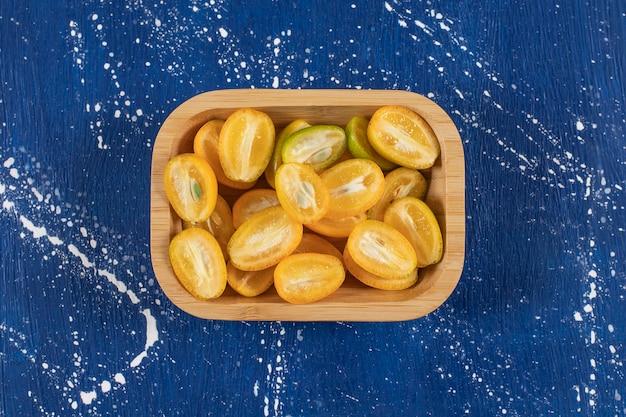 Tigela de madeira com fatias de frutas frescas de kumquat na mesa de mármore.