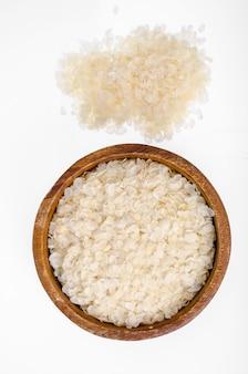 Tigela de madeira com flocos de arroz achatados isolados.