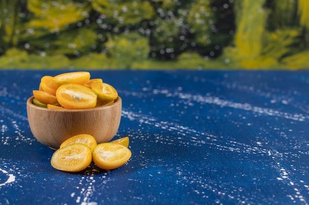 Tigela de madeira com frutas fatiadas de kumquat na superfície de mármore.