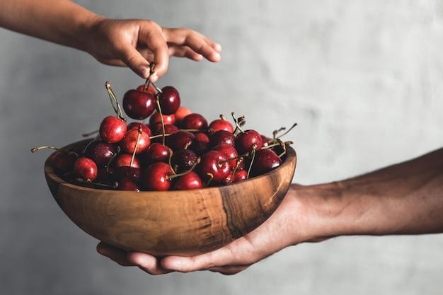 Tigela de madeira com frutas frescas e suculentas. cerejas nas mãos. produto ecológico orgânico, fazenda. não ogm
