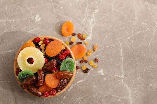 Tigela de madeira com frutas secas na mesa cinza
