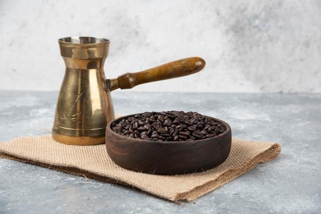 Tigela de madeira com grãos de café torrados escuros e cafeteira na superfície de mármore.