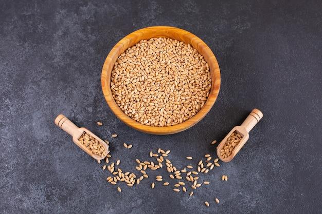 Tigela de madeira com grãos de trigo em fundo preto