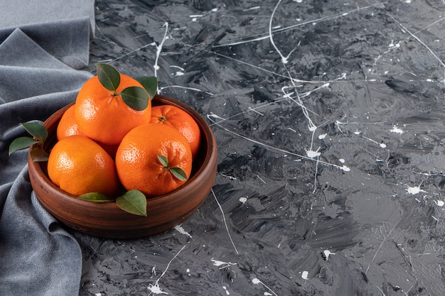 Tigela de madeira com laranjas frescas e suculentas na superfície de mármore